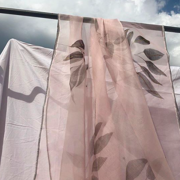 A pink hand-painted fabric hangs on a pole against a plain white sheet