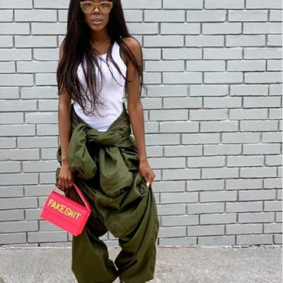 Sonique wearing kaki colored oversized pants with white tank top