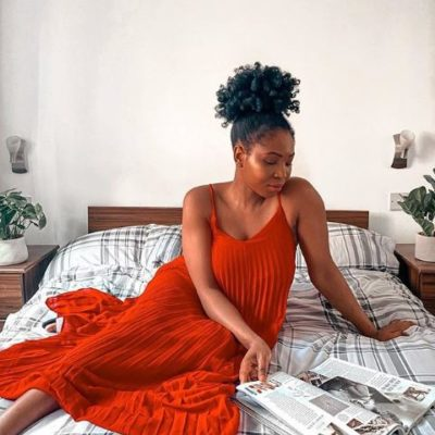Stephy reading a magazine sitting in bed, wearing an orange dress