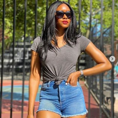 Nikki B. wearing blue denim shorts with a gray shirt tied up at the waist