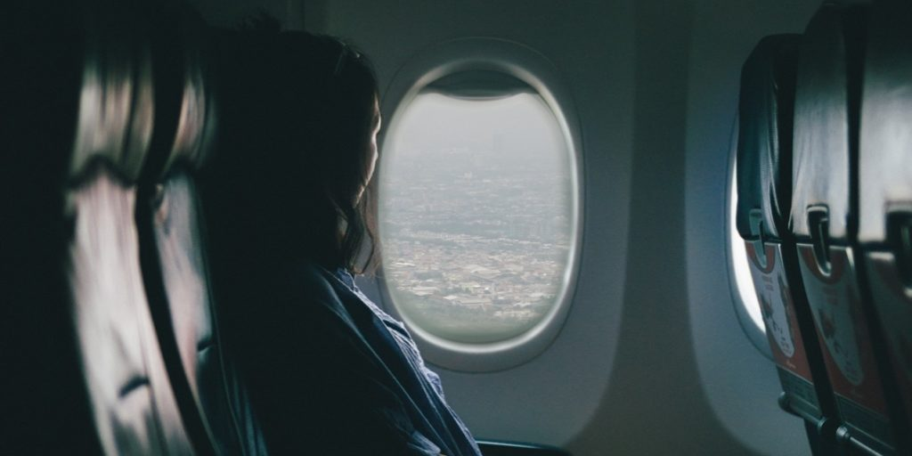 A person looks out of the window while on an airplane. Via Unsplash