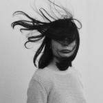 A black and white photo of a woman who hair is whipping around her, covering her face.