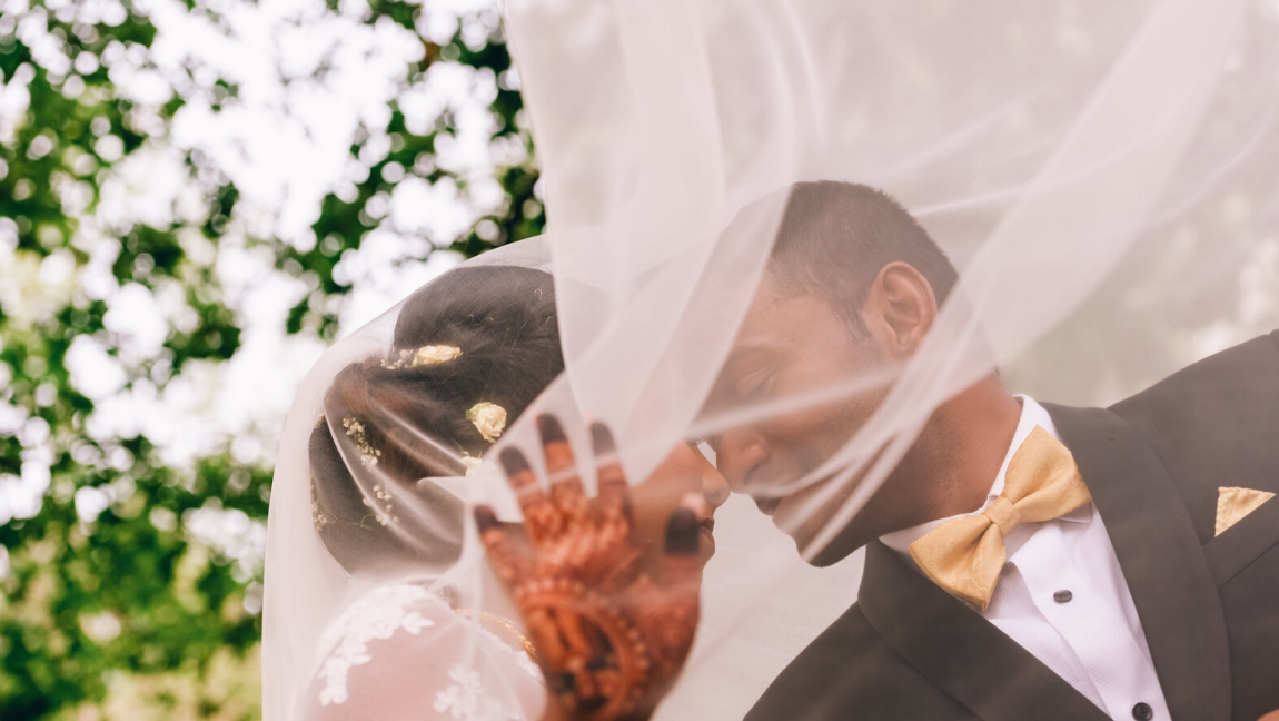 [Image description: A bride blocks the camera as she leans towards the groom.] via Pexels