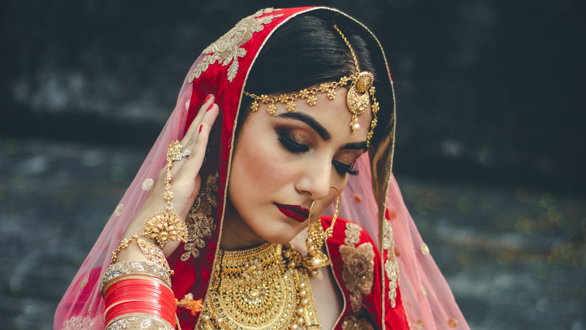 [Image description: Woman dressed in traditional Indian wedding dress looks down.] via Unsplash