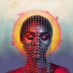 [Image Description: Headshot of Janelle Monae, dressed as a femme robot with her face covered in a silver chain standing eyes-closed in front of a blue background with an orange sun in the center]. Via Atlantic Records.