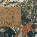 "[Image description: Protester holding up a sign that says ""Puerto Rico Stands w/ Black Lives Matter.""] via Unsplash"