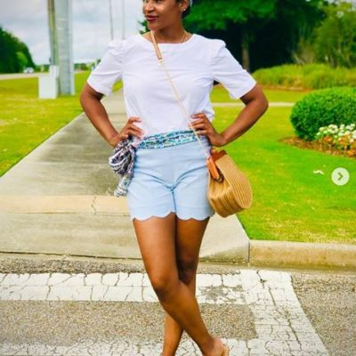 Black woman standing in the street wearing blue shorts and a white shirt