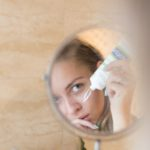 A woman looks into a mirror. as she carefully applies moisturizer onto her face.