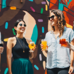 Four women stand together in a semi-circle, holding drinks and laughing in front of a colorful wall.