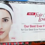 A Fair & Lovely billboard ad.A face of a woman is on the billboard. Half her face depicts a darker complexion, and the other half depicts a 'lighter' complexion. The pink logo of Fair and Lovely is printed next to her face.