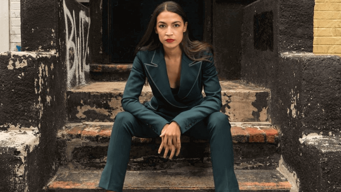 [Alexandria Ocasio-Cortez sits on outdoor stairs looking determined] Via AOC on Instagram