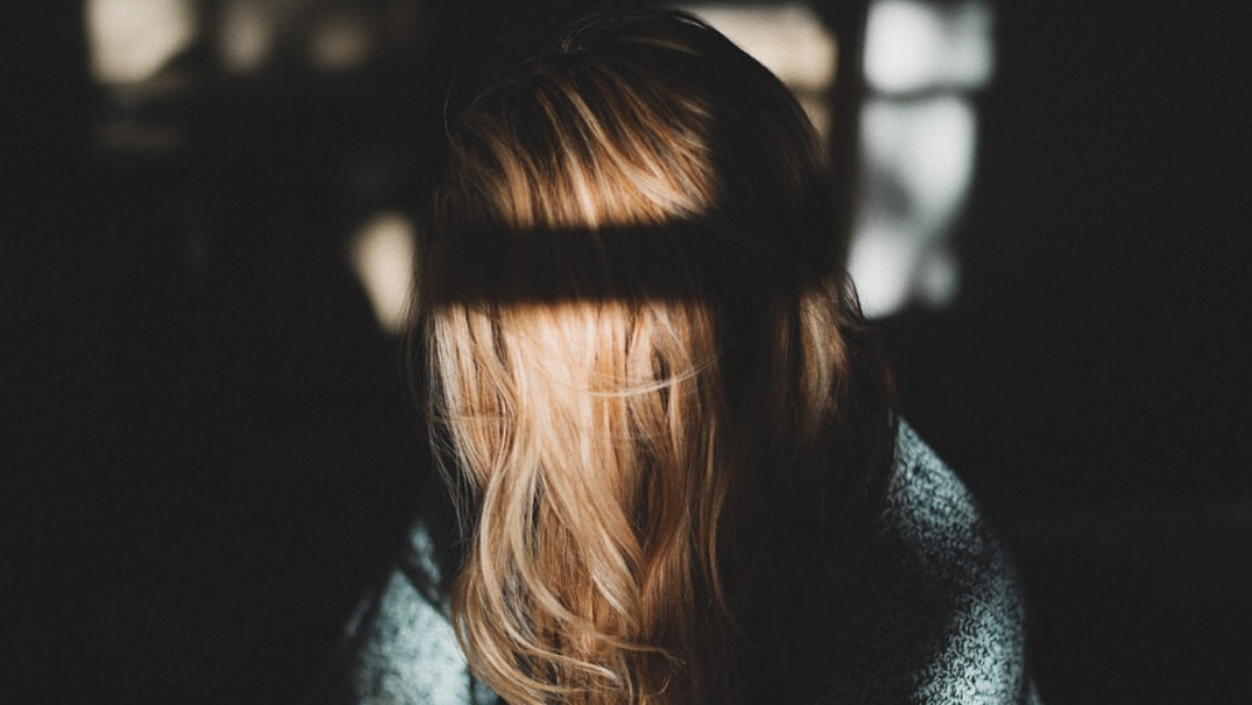[Image description: a photo of a woman with light brown hair, her locks covering her face completely] Via Unsplash