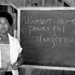 """Audre Lorde standing in front of a chalkboard that says """"Women are powerful and dangerous."""""""