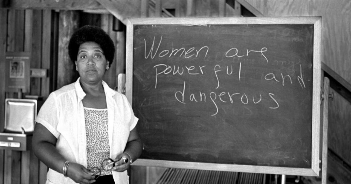 "Audre Lorde standing in front of a chalkboard that says ""Women are powerful and dangerous."""