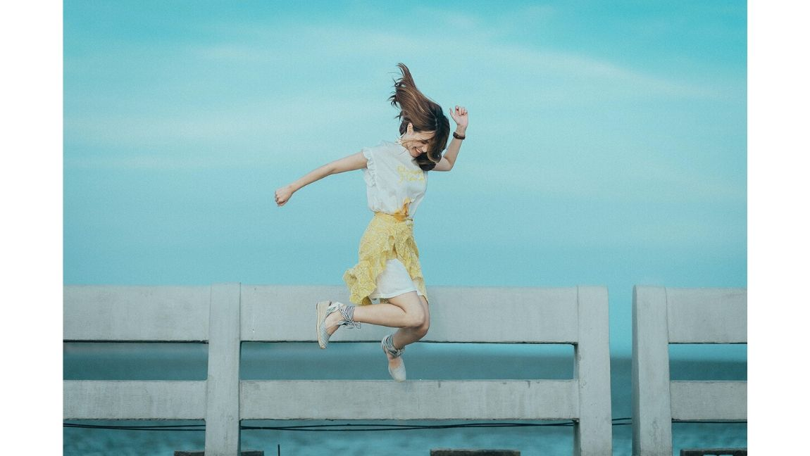 A woman wearing a brightly-colored skirt jumping in front of a blue background.