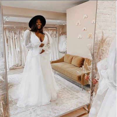 Black woman in a white wedding dress looking at her reflection and smiling