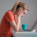Pictured: A young white woman in an orange shirt with a blond ponytail, with her head in her hands. She is looking anxiously at a laptop and has a blue mug beside it.
