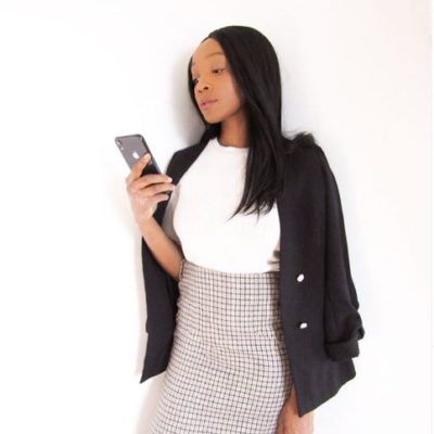 Maya wearing a black and white checkered pattern pencil skirt with a white top and black blazer