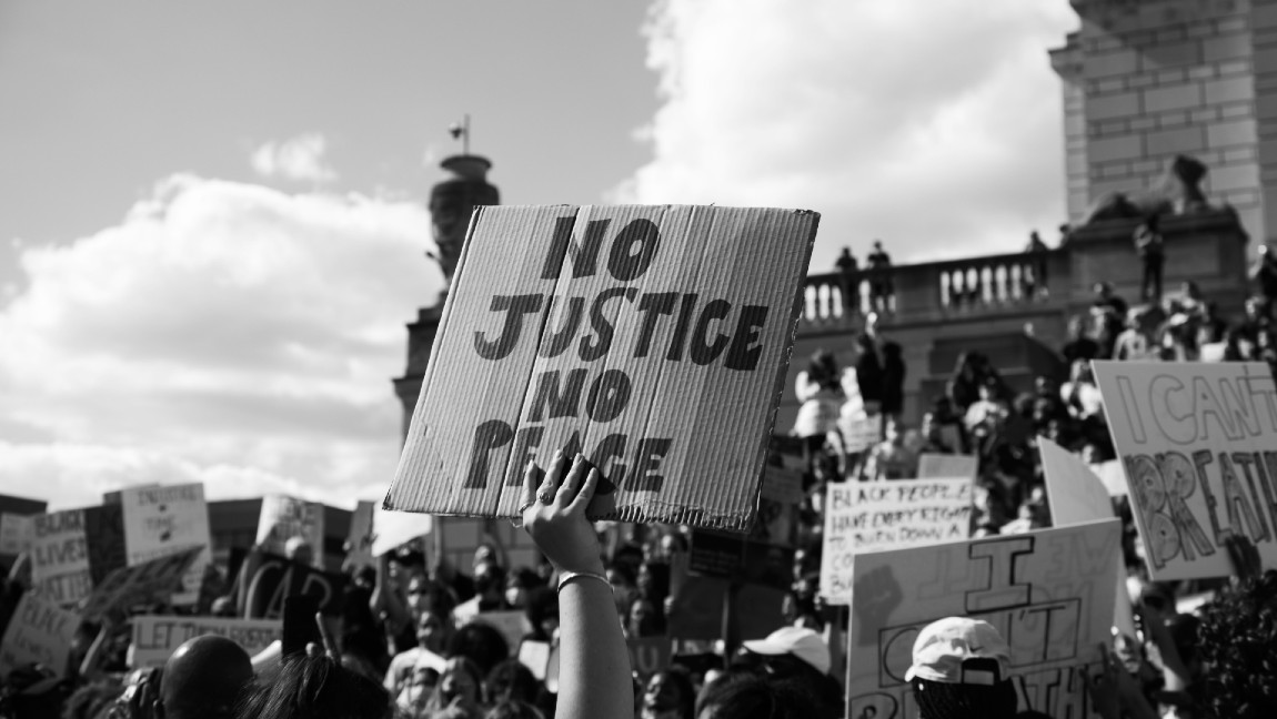 "A sign on a piece of cardboard that reads ""NO JUSTICE, NO PEACE"" held up over a crowd of protestors."