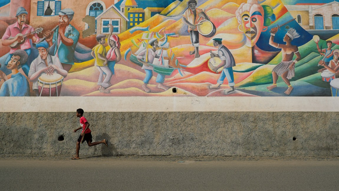 A wall mural with a boy running alongside it.