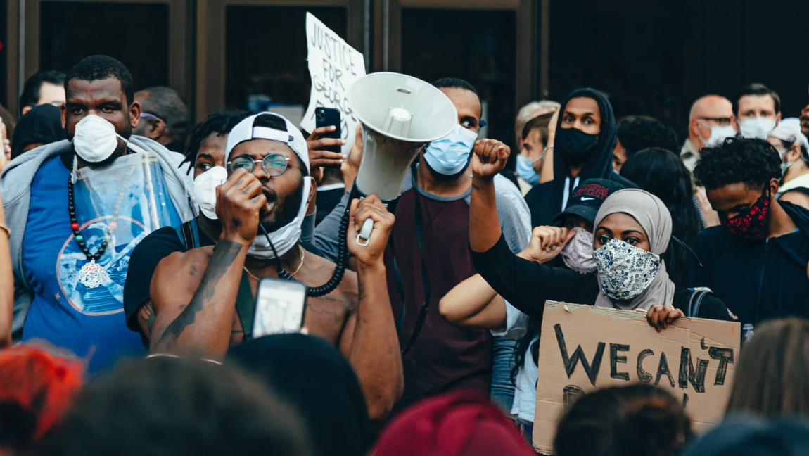 A crowd of protesters at a Black Lives Matter protest in Minneapolis. They are wearing masks and holding signs, one person speaks into a megaphone.