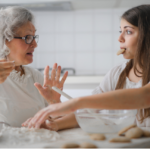 An elderly woman and a girl sit together making cookies.