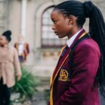 "[Image Description: A still from ""Blood and Water"": teenage girl in a maroon and gold blazer faces to the left with a stern look on her face.] Via Netflix"