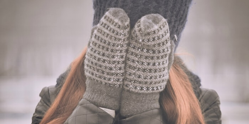 A woman covers her face with gloved hands.