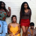 A group of Black women pose together in front of the camera. Via Unsplash