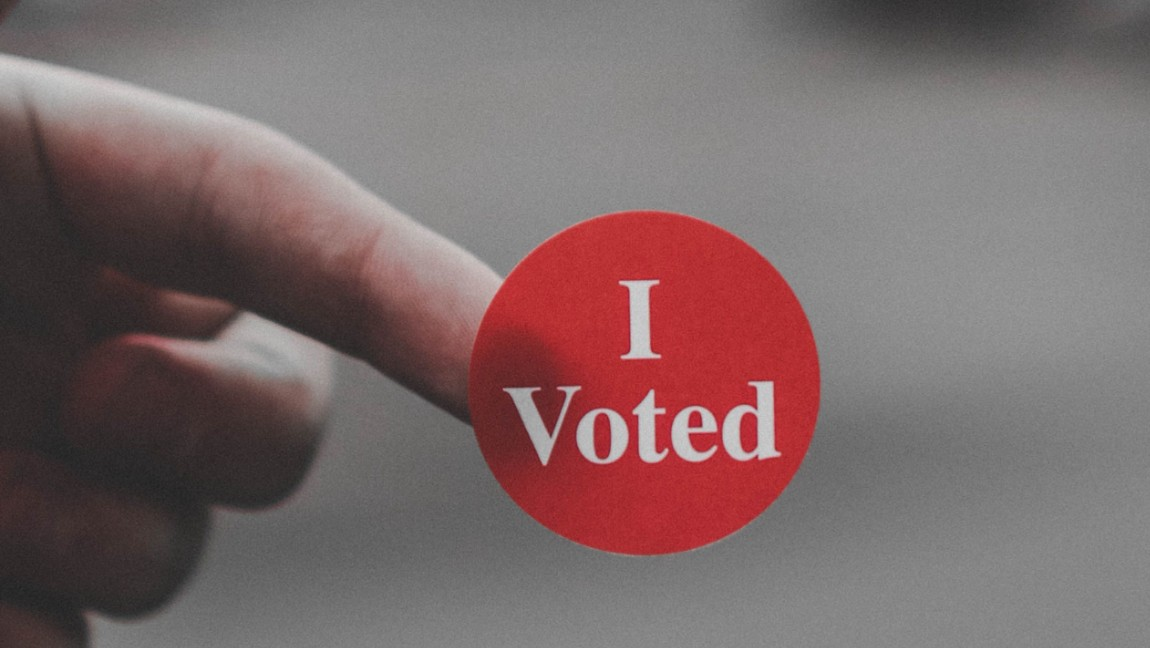 "A person holds a red ""I Voted"" sticker on their finger. Via Unsplash."