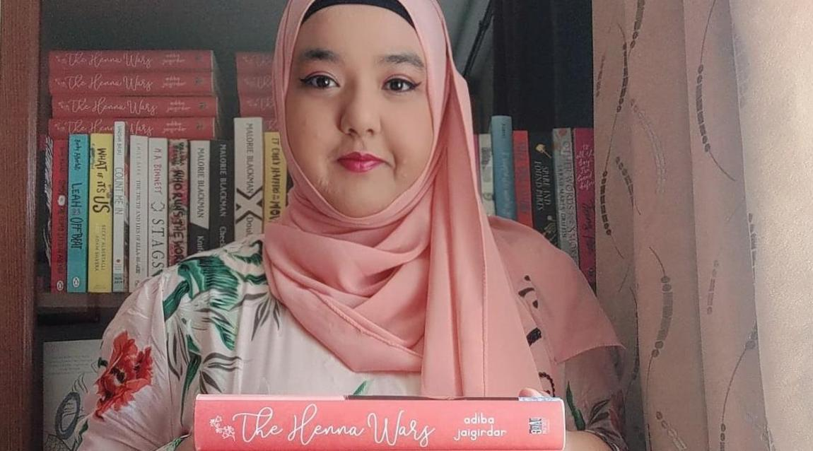 [Image Description: Adiba Jaigirdar holding up her book The Henna Wars in front of a bookcase.] Via Twitter