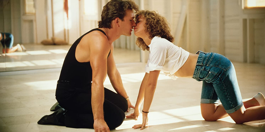 Still from 'Dirty Dancing' (1987). A man dressed in black sits on his heels and a woman wearing denim shorts and a tie-up white shirt stretches over to him.