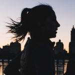 A woman jogging is silhouetted against a sunset.