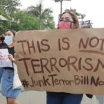 "A woman wearing a mask holds a sign at a protest that says ""THIS IS NOT TERRORISM #JunkTerrorBillNow."""