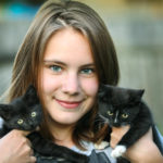 A girl holding two black kittens in her hands.