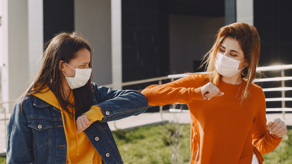 Two women wearing masks touch their elbows together.
