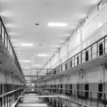 a black and white photo of an empty prison deteriorating with age