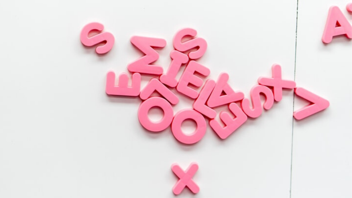 [Image Description: A random assortment of pink letter blocks of the English alphabet are laid on a white surface] Via Unsplash