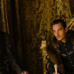 [Image Description: Two dark-haired white men in historical costume in a throne room.Henry Cavill and Rhys Meyers in The Tudors.] via BBC.