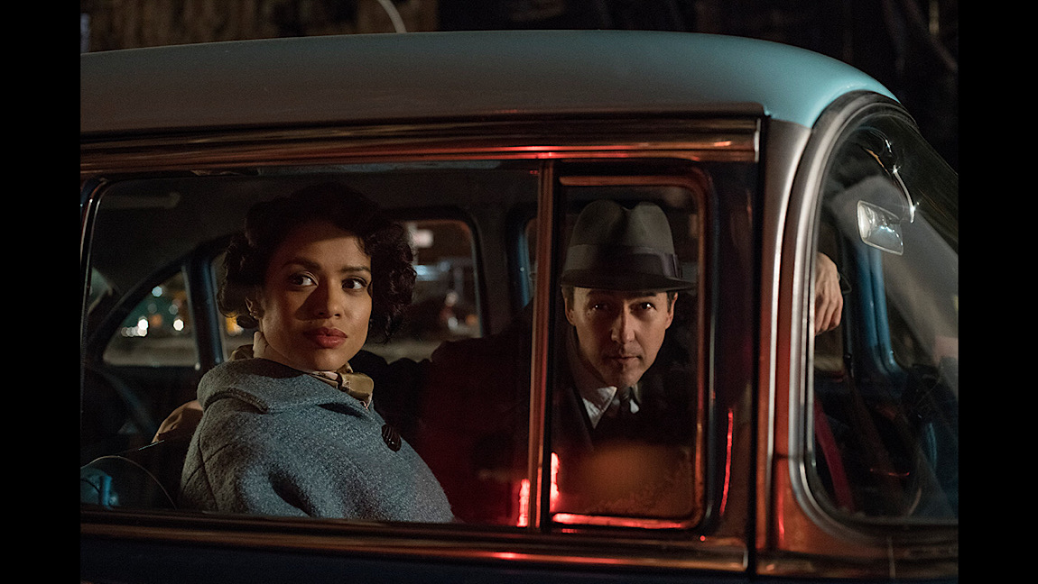 A woman and a man wearing 1950s outerwear look out of a car window.