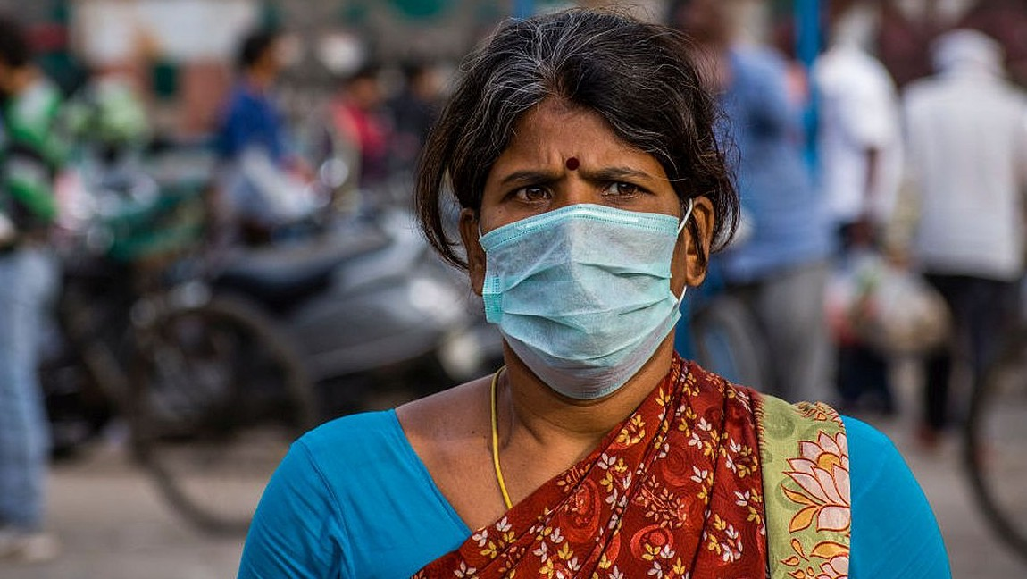 A woman wearing Indian clothing stands in a street with a mask on. Via Getty Images