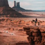 A wide shot of the Oljato-Monument Valley in Navajo County with a man sitting atop a horse on a ridge.