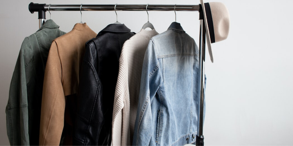 A standing clothes rack holds 5 differently colored jackets and sweaters, and a hat.