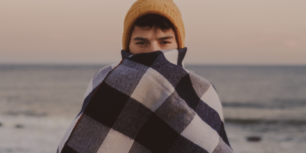 A man bundled up in a white and blue blanket and yellow beanie.
