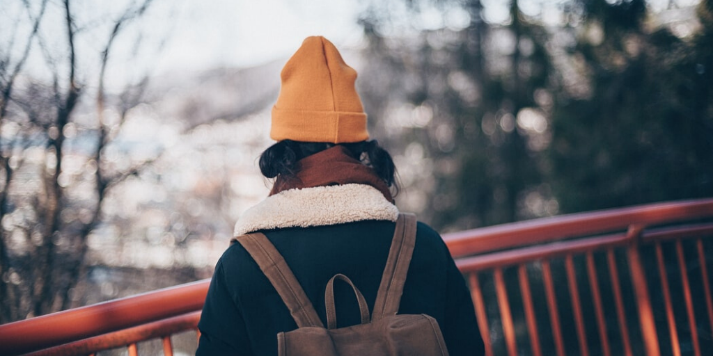A person in pigtails, a yellow beanie, scarf, and jacket, wearing a backpack on their shoulders.