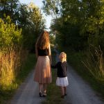A mom and daughter hold hands while walking down a trail.
