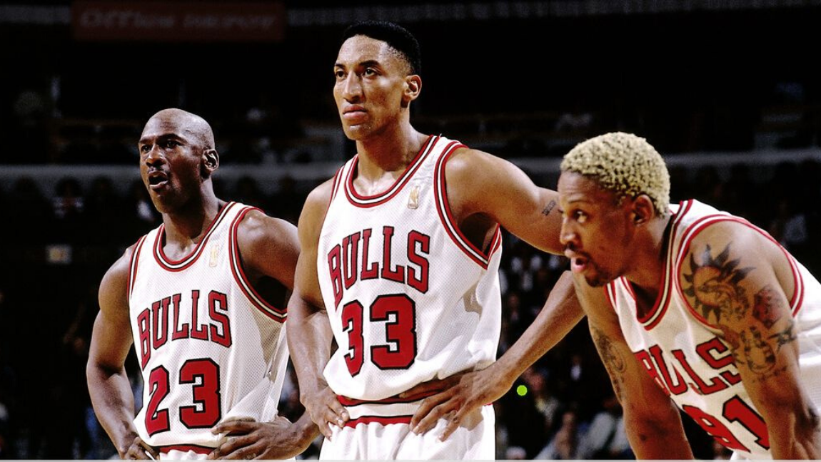 [Image Description: Three Black basketball players in white Bulls jerseys - Michael Jordan, Scottie Pippen, and Dennis Rodman (L-R) - stare offscreen in between plays. Jordan and Pippen have their hands on their hips, while Rodman is bent over, resting his hands on his knees]. Via ESPN.