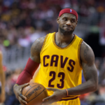 [Image Description: Lebron James, dressed in a yellow Cavs jersey (#23) and a red headband, holds the ball in between plays]. Via Keith Allison, KeithAllisonPhoto.com