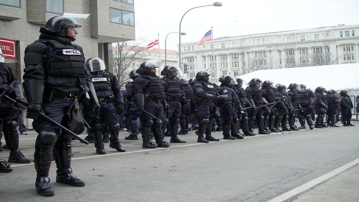 a line of police in riot gear with government buildings in the backdrop