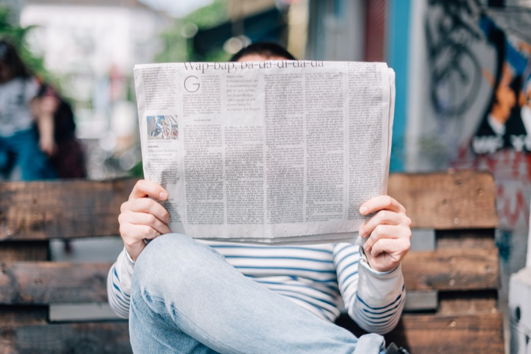 A person reading a newspaper that covers their face. Via Unsplash
